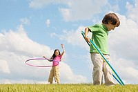 Young boy and girl playing with hula-hoops