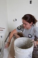 An Americorps volunteer lays tiles while renovating a house in the lower ninth ward damaged by Hurricane Katrina, New Orleans, Louisiana, USA