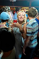 Young woman carrying drinks through a crowd of people in a bar. British pub interior.