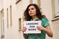 Young woman holding a sign, Looking for work, symbolic picture for the economic crisis