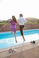 couple jumping into pool,dressed