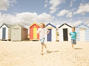 Boys running in front of beach huts