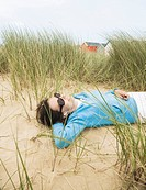 Woman with sunglasses lying in dunes