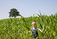 boy playing in corn field