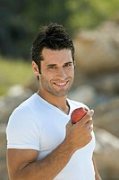 A latin male holding an apple smiling
