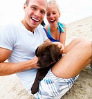 Couple enjoying with pup at beach