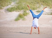 Active guy doing handstand at beach