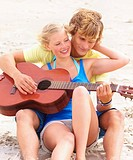 Teen couple playing guitar at beach