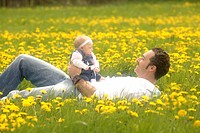 Father with baby, girl, in a spring meadow