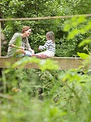 Mother and daughter laughing on bridge