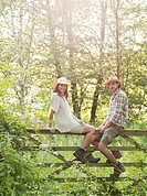 Man and woman sitting on country gate