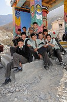 Students wearing uniforms in front of a prayer wheel in Hunder, Nubra Valley, India, the Himalayas