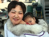 Inuit woman with child on her back, Canada, Nunavut, Gjoa Haven