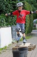 Boy, age 7, Inlineskates, ride over obstacle