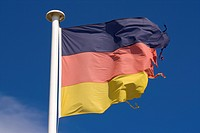 A frayed German flag flutters in front of blue sky