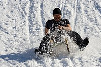 Man sledging down a hill, wearing a t_shirt, Zillertal, Austria