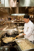 A chef cooking shrimps in a wok at the Palette Dining Studio in the MGM Grand casino, Detroit, Michigan, USA
