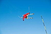 Skier jumpinh, against blue sky, with a slalom pole