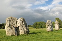 Man touching a big stone, outstretched arms, stone circle, Avebury, Wiltshire, England, Great Britain, Europe