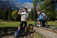 Mountainbike riders, male and female resting at a well, he is drinking from a bike bottle, Kleiner Ahornboden forest district, Hinterriss, Tyrol, Aust...