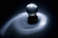 Crystal ball on wood stand black background and spotlight