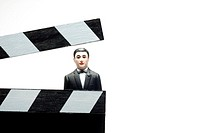Man in a tuxedo wrapped in in front of a movie clapper board