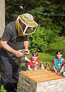 Royal Oak, Michigan - Beekeeper Rich Wieske teaches members of a Girl Scout troop about honey bees and beekeeping  Here he is using a bee smoker to ca...