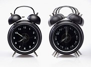 Two alarm clocks one still ringing - on white background