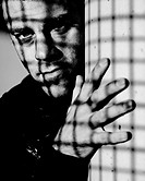 Young man behind bars  Black and white  Conceptual