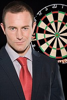 Businessman standing next to a dartboard (thumbnail)