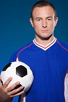 Serious looking footballer with ball