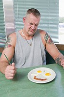 Angry man looking at smiling meal