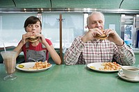 Girl and old man eating burgers in a diner