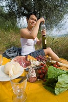 Woman opening bottle of wine in preparation for picnic under olive trees