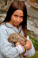 child holds rabbit in arms, France