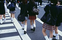 School girls in uniforms walking across cross walk