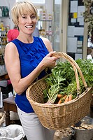 Woman in store with basket of vegetables