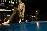 Young woman by car in gas station