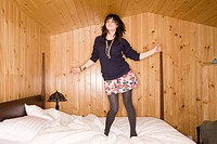 Young woman dancing on bed (thumbnail)