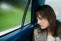 Young woman asleep in car