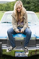Young woman sitting on car with cellphone
