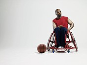 Wheelchair basketball player and ball on floor
