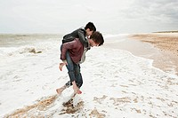Man giving girlfriend piggyback in the sea (thumbnail)