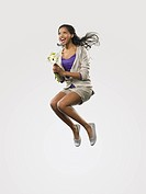 Young woman jumping with flowers