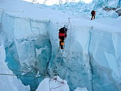Viennese climber Geri Winkler on a ladder overcoming a crevasse of Khumbu Icefall, ca.5600 m, Mount Everest, Himalaya, Nepal