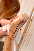 foot with ballet shoe on ballet bar, female ballet dancer stretching leg.