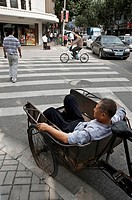 a worker sits in a truck on the street. Shanghai, China