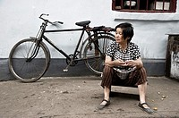 woman sitting in the street. Shanghai, China