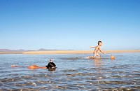 Boy, 4 years, trying to catch fish with a net, girl, 8 years, making first attempts at snorkeling in shallow water, on the beach of Fuerteventura, Can...