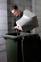 Man disposing of obsolete computer technology in a wheelie bin